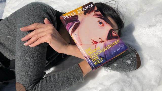 Annette König liegt im Schnee und hat über dem Gesicht das Buch «Die sanfte Gleichgültigkeit der Welt» von Peter Stamm liegen.