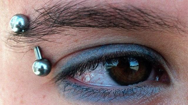 Nahaufnahme eins Auges mit silbernem Augenbrauenpiercing