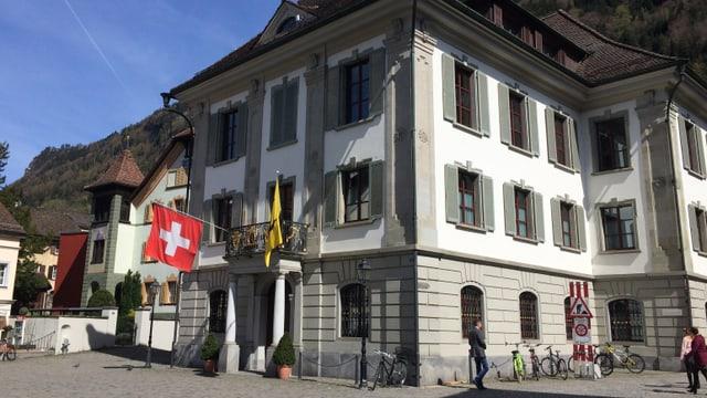 Geschmücktes altes Gebäude (Rathaus des Kantons Uri) auf einem Platz.