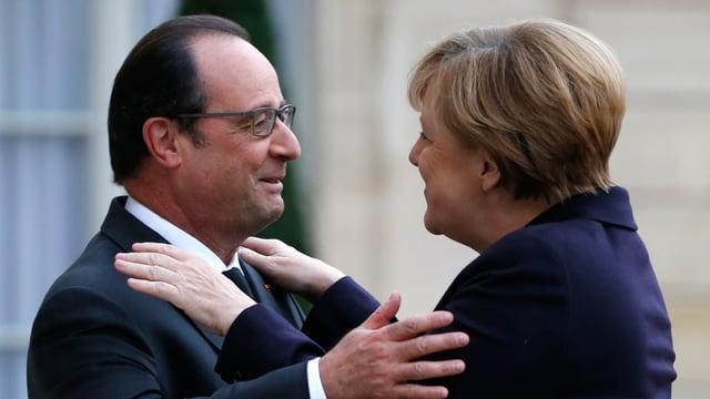 François Hollande und Angela Merkel geben sich eine Umarmung