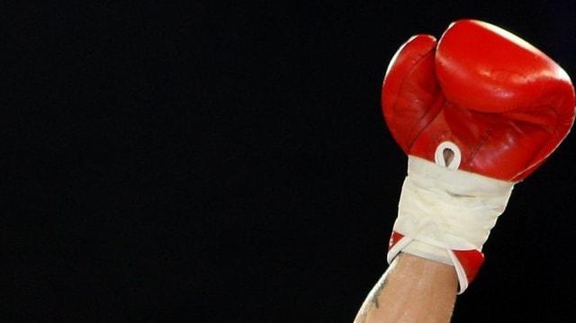 Erhobene Faust mit rotem Box-Handschuh