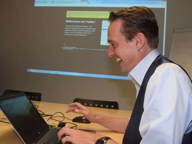Moderator Florian Inhauser sitzt an einem Computer und freut sich.