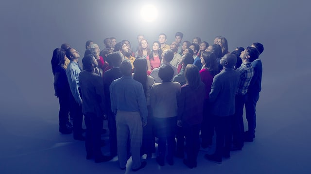 Ein Gruppe von Menschen, zu einem Kreis zusammengerückt, auf ein Licht in der Mitte schauend.