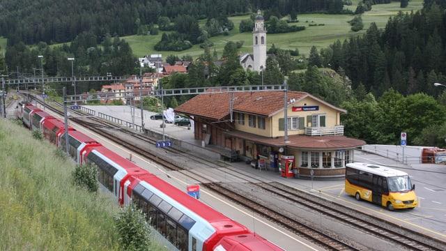 La staziun da Casti cun in auto da posta sin la plazza ed in tren da Viafier retica davant.