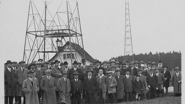 Ein schwarz-weiss-Bild einer Gruppe Männer in Mändeln und Hüten, dahinter das Haus, in dem sich das Studio befand.