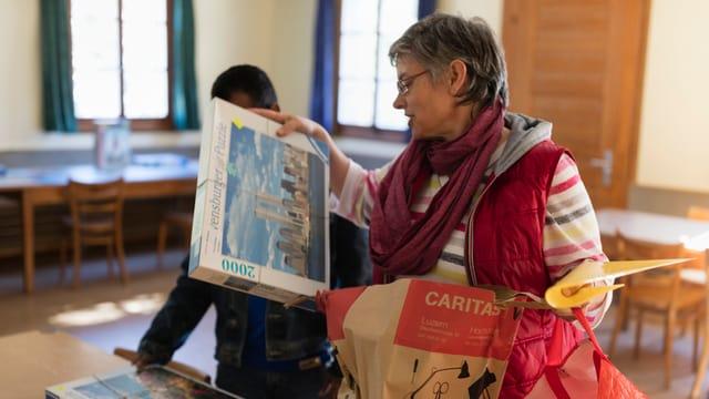 Annemarie Wuerms von Caritas, Mitte, bringt Asylsuchenden Puzzles, aufgenommen am 20. April 2016 in einer temporaeren Asylunterkunft auf der Rigi-Kloesterli. Die Asylsuchende leben waehrend der Zwischensaison in einem von der Caritas als Asylunterkunft genutzten Ferienhaus auf der Rigi-Kloesterli. Zum Zeitpunkt der Fotodokumentation waren 14 von 50 Plaetzen mit Asylsuchenden aus den Laendern Sri Lanka, Afghanistan und Iran besetzt. Die Asylsuchenden lernen Deutsch, verrichten Kuechen-, Haushalts- und Reinigungsarbeiten. In ihrer Freizeit spielen sie beispielweise Volleyball und gewoehnen sich an das Leben in der Schweiz.
