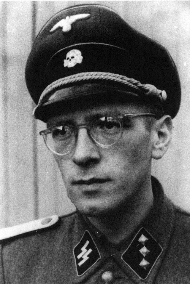 Schwarzweissfoto: Ein Mann mit Brille in Uniform: Am Kragen sind die Runen der SS zu sehen, am Hut das Totenkopf-Symbol.
