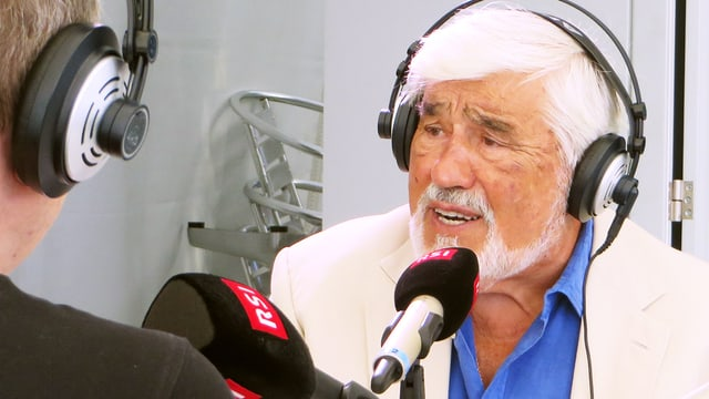 Mario Adorf sitzt vor einem Mikrofon, er hat Kopfhörer aufgesetzt.