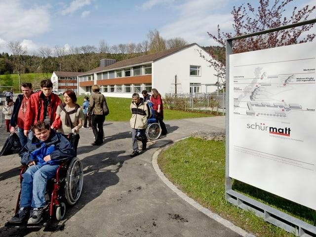 Mehrere Betreuer schieben einige Behinderte mit Rollstühlen über das Gelände der Stiftung Schürmatt