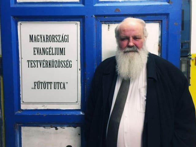 Gábor Iványi mit langem, weissem Bart vor einer Türe.