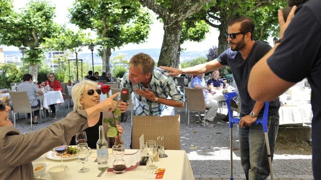 Reto und Bligg schenken einer Restaurant-Besucherin eine Rose