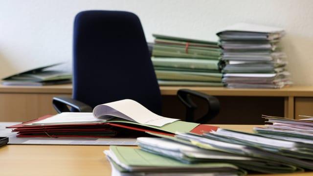 Ein Schreibtisch mit vielen Akten drauf