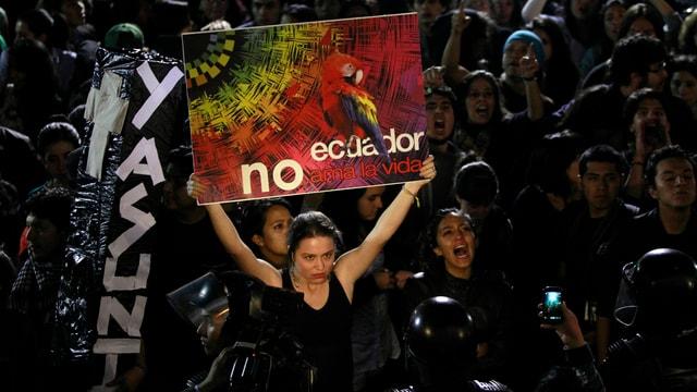Eine Frau hält ein Plagat inmitten einer Menschenmenge