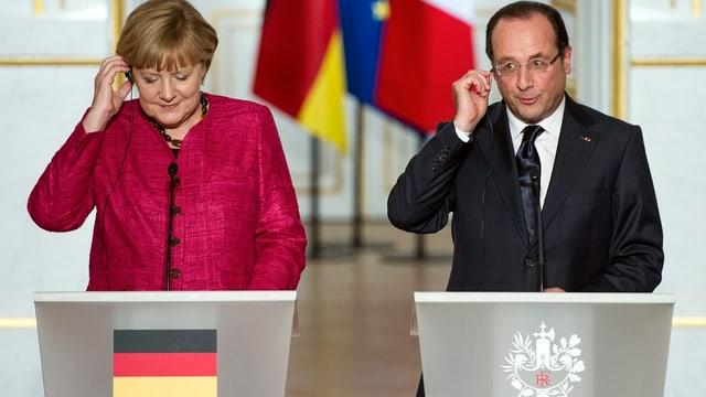 Die deutsche Bundeskanzlerin Angela Merkel (links) und Frankreichs Präsident François Hollande (rechts) hinter Rednerpulten