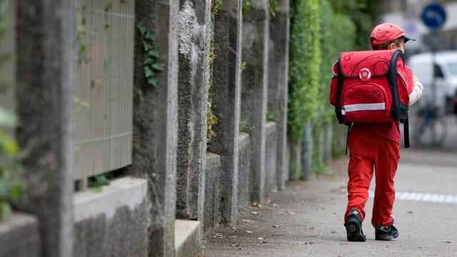 Ein kleiner Junge auf dem Schulweg mit dem Rücken zur Kamera