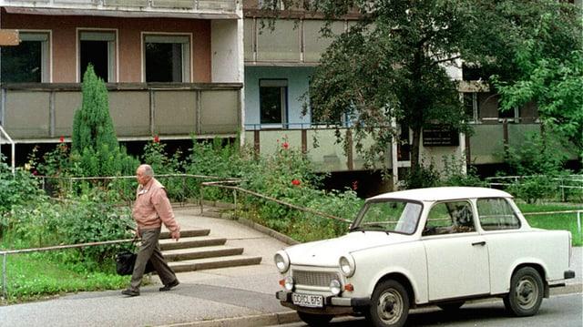 Ein Trabant steht vor einem DDR-Plattenbau
