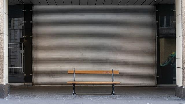 Leere Parkbank vor geschlossenem Geschäft