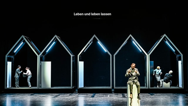 """ganze Bühne mit Häuserrahmen, Hausmeister sitzt vorne. Schriftzug an der Wand: """"Leben und leben lassen"""""""