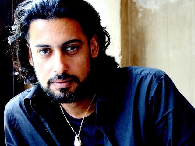 Der irakische Autor Abbas Khider mit blauem Hemd und langen schwarzen Haaren.