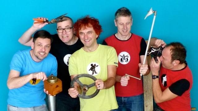 Fünf Männer in farbigen T-Shirts mit diversen Gegenständen in den Händen