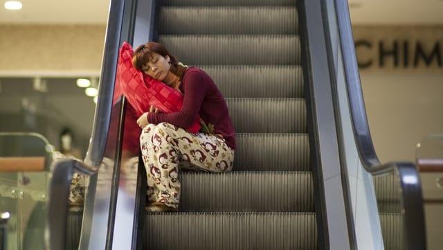 Schlafwandelnde Frau auf einer Rolltreppe