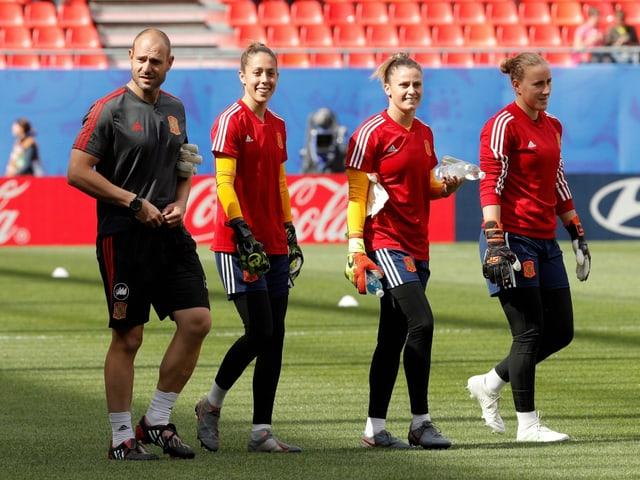 Vier spanische Spielerinnen marschieren über den Rasen.