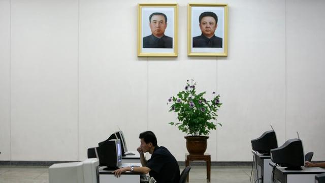 Ein Nordkoreaner sitzt an einem Computer, über ihm an die Wand gehängt ein Portrait von Kim Il-sun und Kim Jong-il.