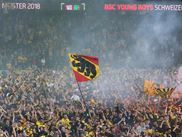 Eine Berner Fahne in den jubelnden Fans