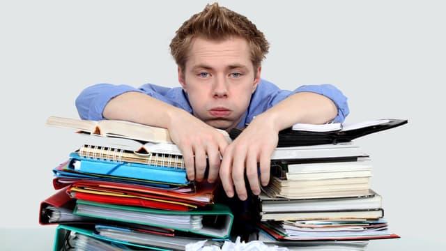 Ein Mann schaut frustriert und stützt sich auf Bücher