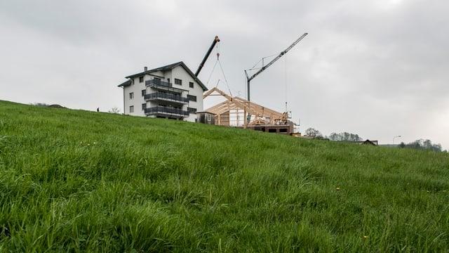 Wiese mit Häusern und Baukran