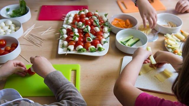 Kinder sitzen an einem Mittagstisch.