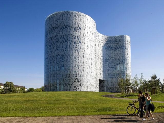 Die Bibliothek von aussen zeigt eine stromlinienförmige Fassade mit verschiedenen Strukturen.