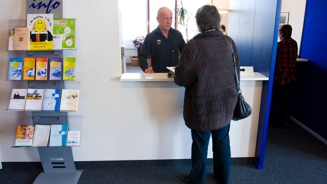 Frau steht an einem Schalter der Arbeitslosenversicherung