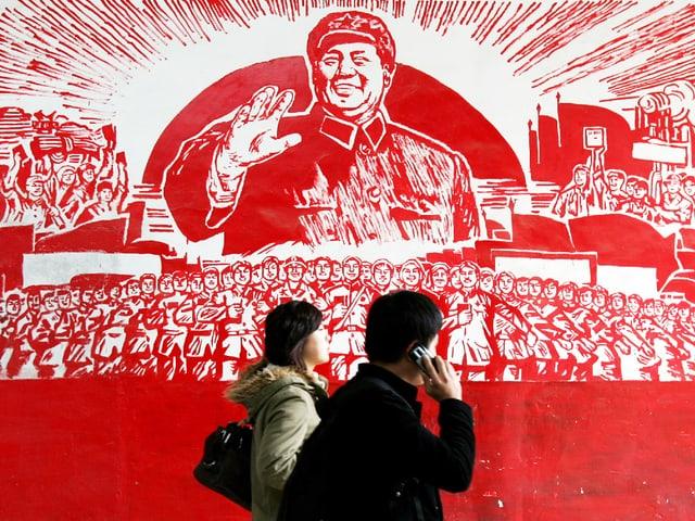 Zwei Menschen vor einem grossen roten Wandgemälde, das Mao Zedong zeigt.