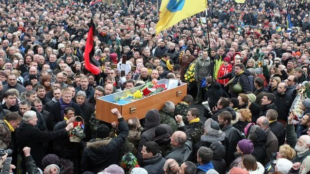 Sarg wird durch eine Menschenmenge getragen.
