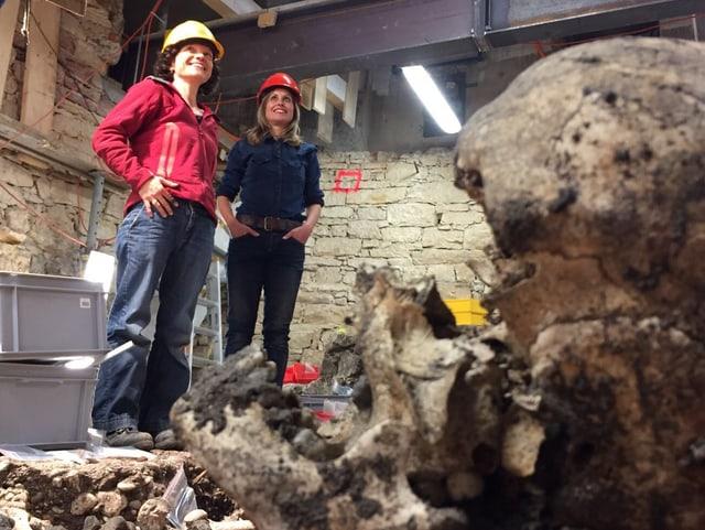 Vorne im Bild ein kaputter Totenschädel in einer offenen, grossen Baugrube, hinten zwei Frauen.