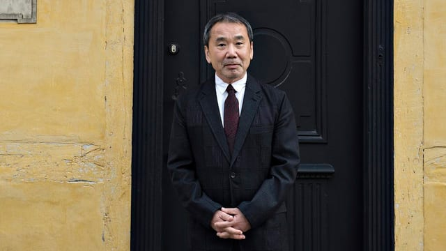 Haruki Murakami steht im Anzug und mit verschränkten Händen vor einer Haustür.