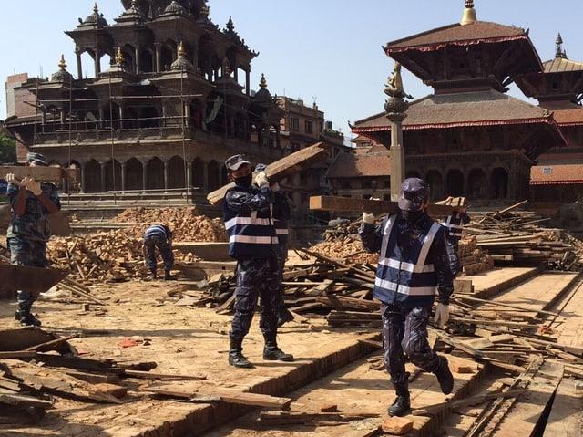 Sicherheitskräfte tragen Holzstücke vom Durbar Platz in Kathmandu.