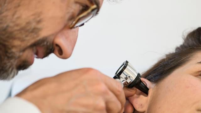 Hausarzt schaut Patientin in ihr rechtes Ohr.