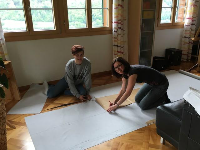 Zwei junge Frauen mit Stoff und Schere auf Boden.