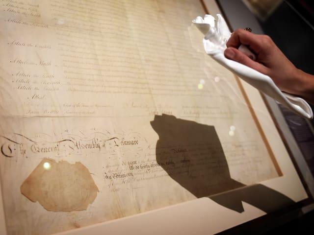 Eine Hand putzt mit einem Lumpen ein wertvolles Stück Papier, geschützt hinter Glas.
