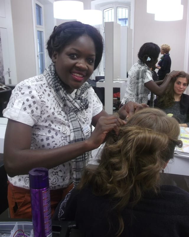 Die afrikanische Coiffeuse Loide Kondja frisiert einer Kundin die Haare.