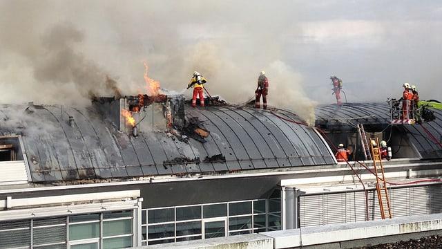 Feuerwehrleute löschen einen Brand auf dem Dach eines Fitnesscenters.