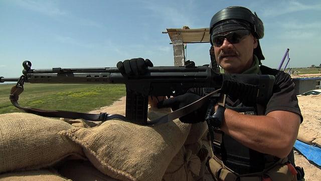Ein Mann mit T-Shirt und Sturmgewehr auf einem Beobachtungsposten.