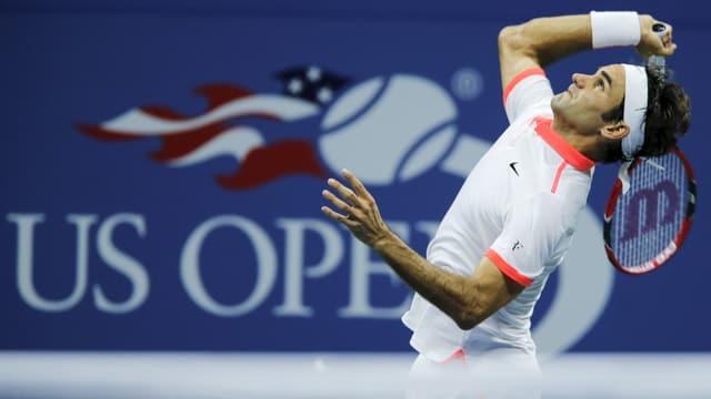 Roger Federer schlägt auf, im Hintergrund das Logo der US Open.