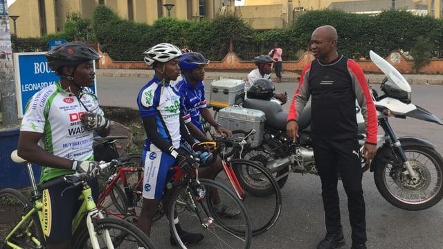 Drei Rennradfahrer stehen vor einem weiteren Mann, der zu ihnen spricht.