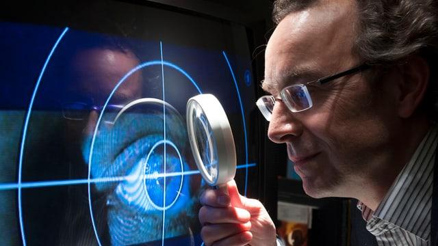 Ein Mann blickt durch eine Lupe auf einen Schirm, auf dem das Tatort-Logo zu sehen ist - das Auge in einem Fadenkreuz.