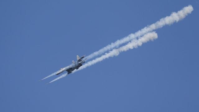 Kampfjet in der Luft, schiesst Raketen ab, Rauchwolken