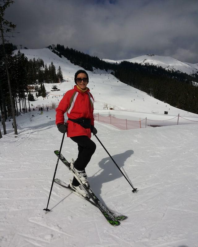Eine Frau auf der Skipiste in schwarzen Hosen und einer roten Jacke.