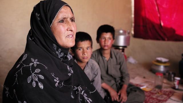 Frau mit zwei Kindern, sitzt am Boden.